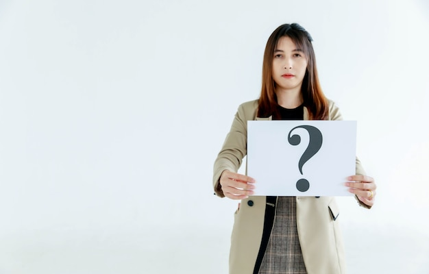Studio shot of doubtful female officer staff in business suit look at camera holding question mark paper cardboard sign showing curiosity thinking for answers on white background.