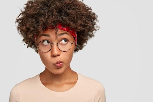 Studio shot of doubtful girl purses lips
