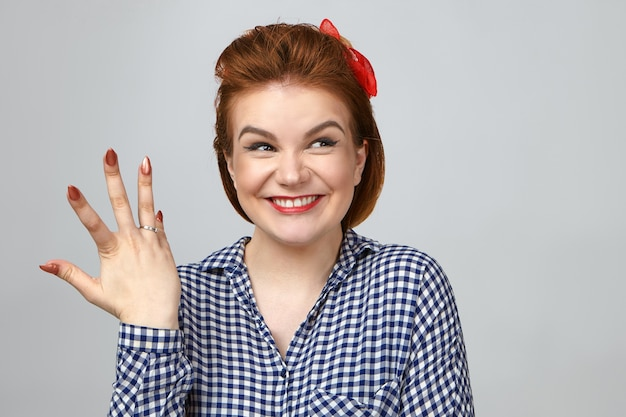 Studio shot of ecstatic young red haired female smiling broadly, being excited after her boyfriend proposed to her. overjoyed girl showing engagement ring on her finger, happy with marriage proposal