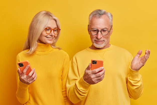Studio shot of elderly man looks puzzled at smartphone display has some problem raises palm his wife tries to help her stand closely to each other isolated over yellow wall