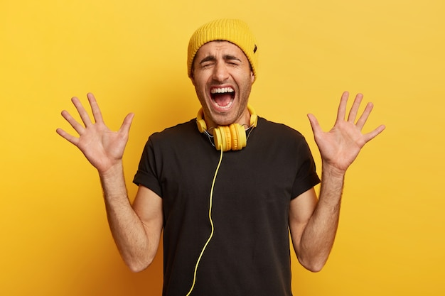 Studio shot of emotional hipster guy shouts and gestures actively, shows palms at camera