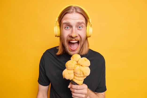 Studio shot of emotional redhead guy dirty after eating cone ice cream enjoys yummy summer dessert effords himself tasty food listens audio track in headphones