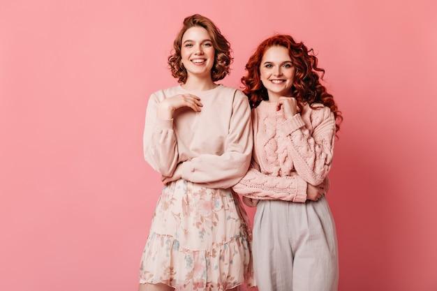 Studio shot di incantevoli ragazze isolate su sfondo rosa. due amici alla moda che esaminano macchina fotografica con il sorriso.