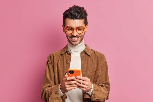 Studio shot of european man blogger types text messages on smartphone smiles pleasantly