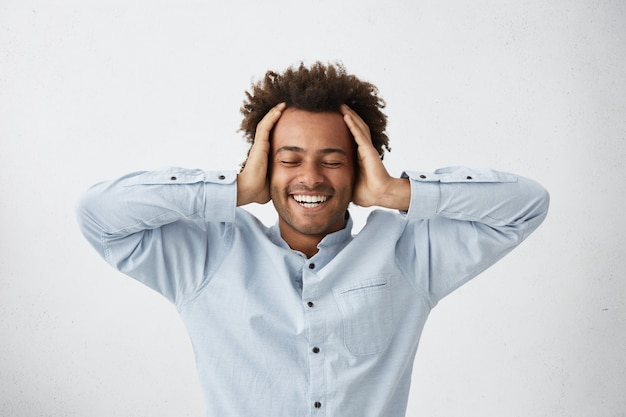 Studio shot of excited lucky young dark-skinned man smiling broadly closing eyes