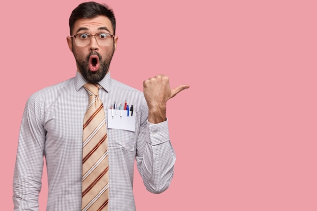 Studio shot di esperto dipendente di sesso maschile con la bocca ampiamente aperta, si sente sorpresa e stupore, indossa una camicia elegante, punti da parte in uno spazio vuoto