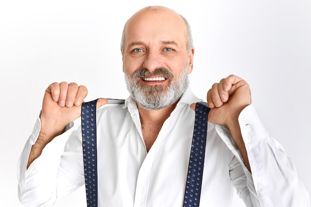 Studio shot of fashionable handsome elderly bearded man in his sixties posing isolated wearing elegant clothes, adjusting suspenders, smiling