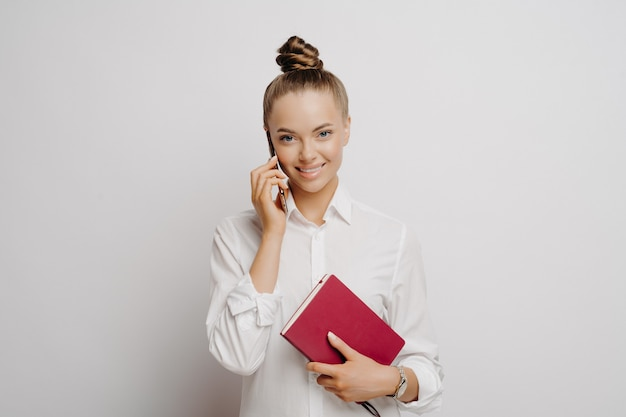Studio shot of female manager in white shirt discusses business issues via smartphone while holding red note book, young business woman satisfied with work results while standing against light wall