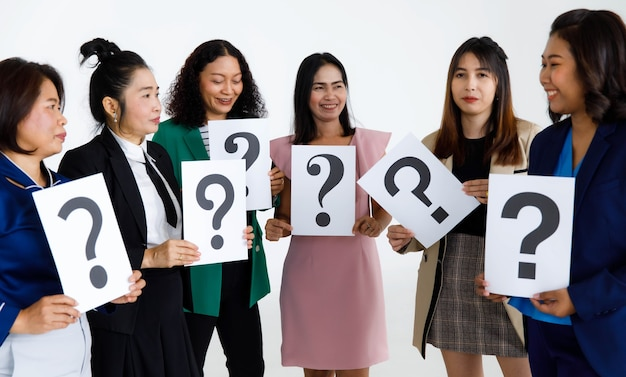 Studio shot of female staff officer in business suit wears stand hold variety fonts of question mark paper sign in hands doubtful for answers on white background.