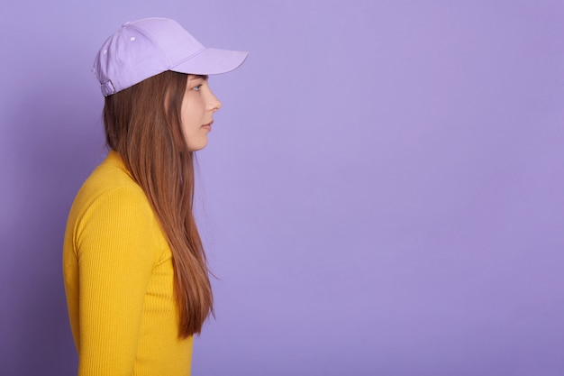 Studio shot of female wearing baseball cap and yellow shirt, side view of attractive female looking straight ahead