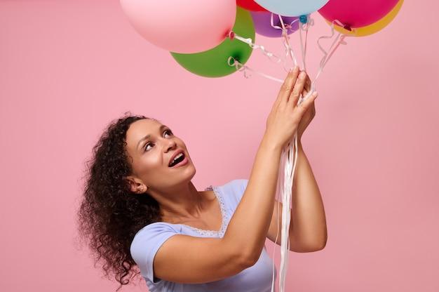 コピースペースでピンクの背景に立って幸せそうに笑っているカラフルなエアボールに手を伸ばす驚きの女性の広告のためのスタジオショット。お祝い、休日、記念日、ギフトの概念。