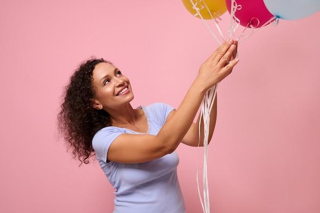 コピースペースのあるピンクの背景に幸せそうに笑っている色とりどりの気球に手を伸ばす陽気なきれいな女性の広告のためのスタジオショット。お祝い、休日、記念日、ギフトの概念。