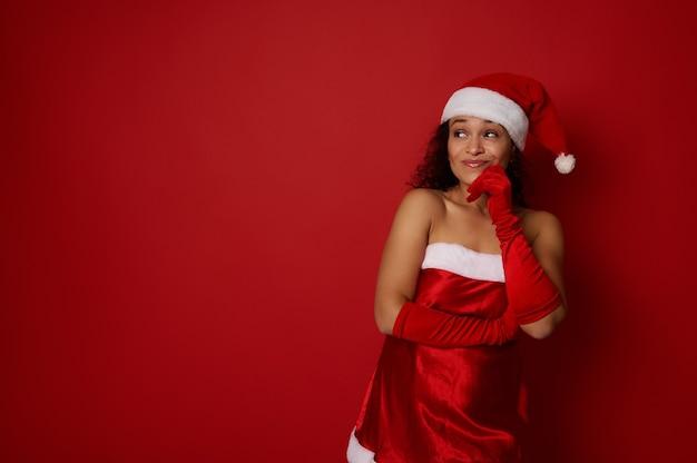 크리스마스와 새해 광고를 위해 촬영된 스튜디오는 산타 카니발 의상을 입은 수심에 찬 신비한 아름다운 여성이 입술 근처에 손가락을 대고 빨간색 배경의 복사 공간을 신중하게 올려다보는 광고를 촬영했습니다.