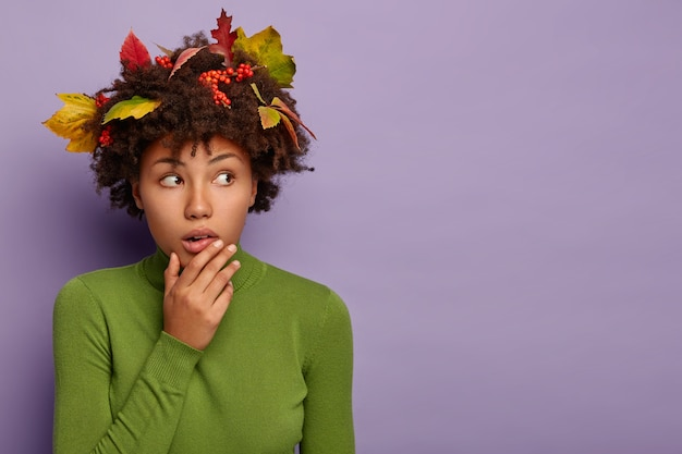 Studio shot of frightened impressed afro american woman touches chin and looks aside, dressed casually, has curly hairstyle with autumn foliage, isolated over purple wall.
