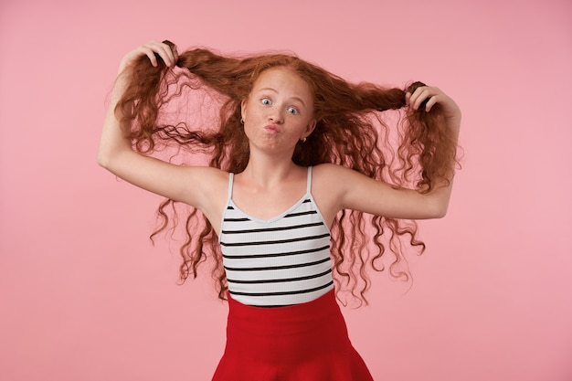 Studio shot of funny redhead female kid with long curly hair making faces over pink background, looking at camera with raised eyebrows and pursing lips, wearing festive clothes