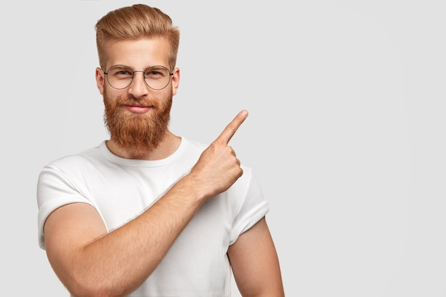 Studio shot of ginger hipster with thick beard, trendy haircut, has serious expression, points with index finger at upper right corner