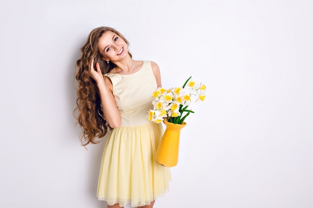 A studio shot of a girl standing and holding a yellow vase with flowers.