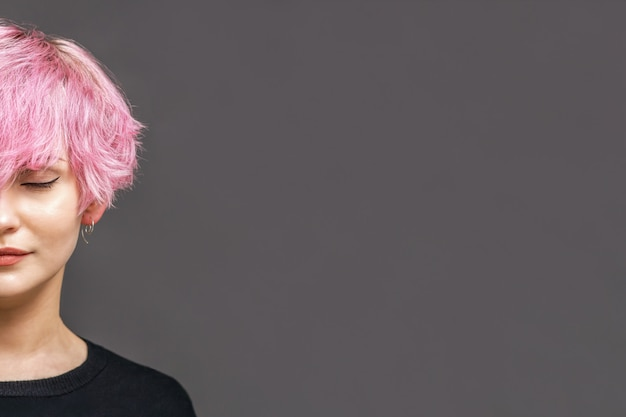 Studio shot of girl with nice pink hairdo, red lipstick on her lips, stands with closed eyes. copy space