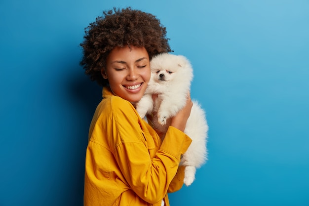 Studio shot of glad female model holds fluffy pet closely to face after grooming, smiles with happiness