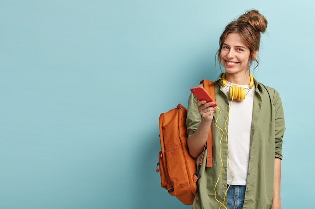 Studio shot of glad female model holds modern smartphone gadget, reads publication and listens audio message in headphones