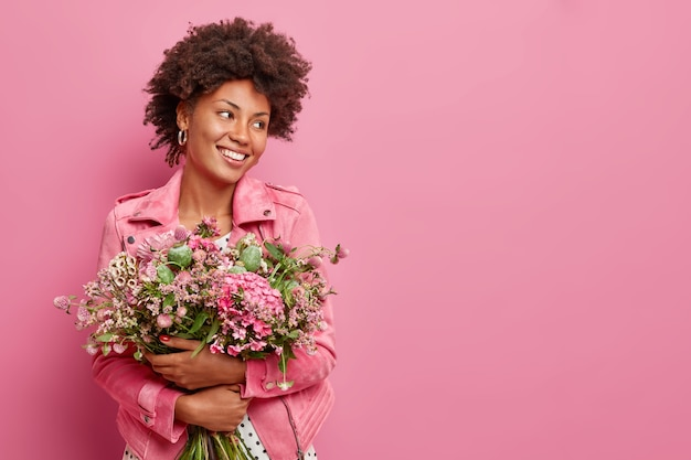 Studio shot of glad woman holds big bouquet of flowers celebrates spring holiday smiles gladfully looks away poses against pink wall with copy space for your promotion