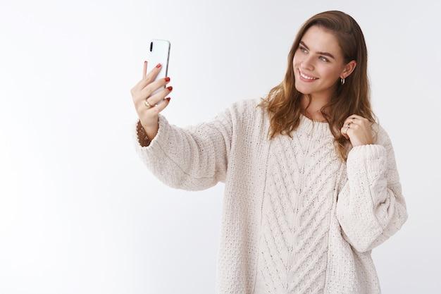 スタジオショットグラマーモダンで魅力的な女性がスタイリッシュでゆったりとした居心地の良いセーターを着て腕を伸ばし、スマートフォンを傾けて頭を傾けて笑顔のディスプレイを撮影してかわいいセルフィー投稿をオンラインで撮影、白い背景