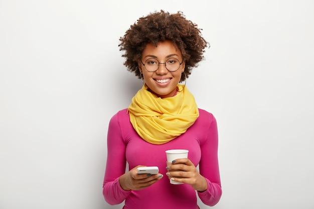 Lo studio ha sparato di bello modello femminile tiene il cellulare moderno, rende la pianificazione nel pianificatore mobile, indossa gli occhiali, dolcevita rosa e sciarpa, pone sopra il muro bianco