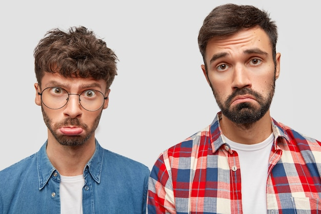 Studio shot of good looking two beared men feel insult, curve lips, have displeased expressions, being offended because of something, pose against white wall