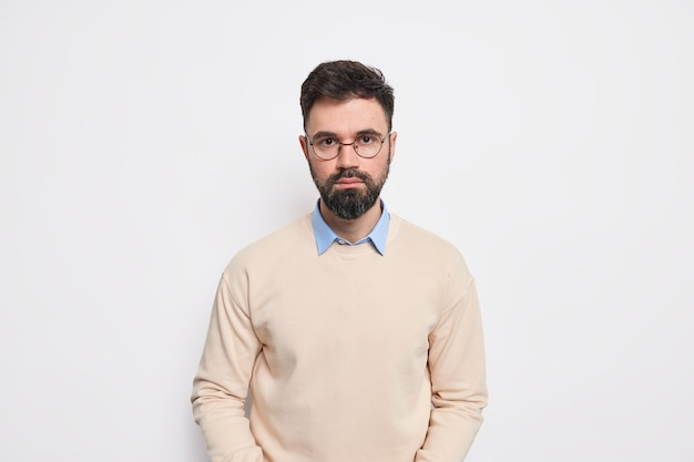 Studio shot of handsome bearded adult european man looks directly, with serious expression has determined face dressed in neat jumper round spectacles