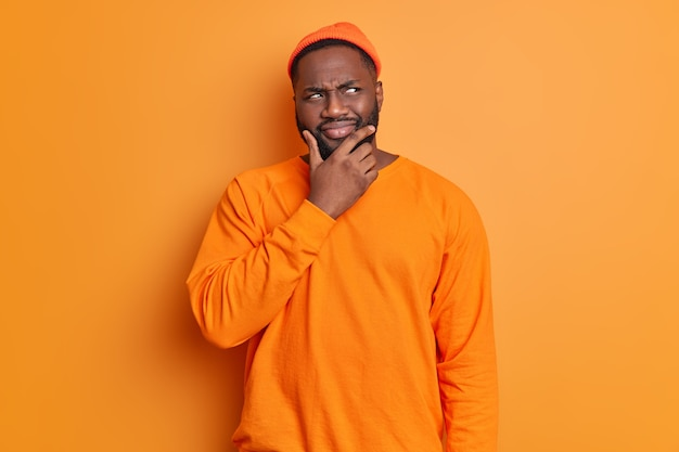 Studio shot of handsome bearded man holds chin looks thoughtfully aside thinks deeply about something wears hat and sweater poses against bright vivid orange wall