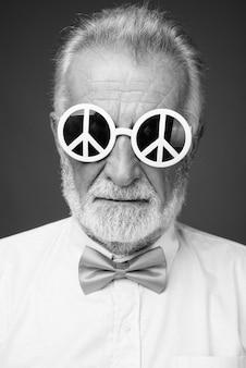 Studio shot of handsome bearded senior man wearing stylish clothes, black and white