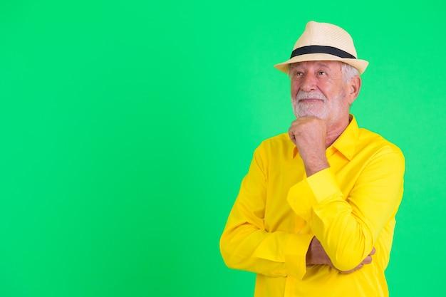 Studio shot of handsome bearded senior tourist man against green background