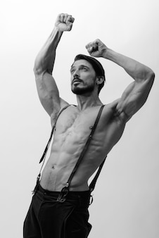 Studio shot of handsome man flexing both arms while looking up shirtless