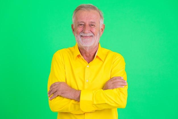 Studio shot of handsome senior bearded businessman against green background