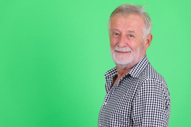 Studio shot of handsome senior bearded man against green background