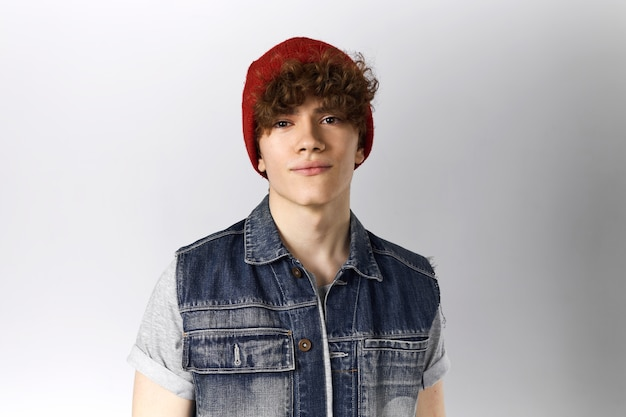 Studio shot of handsome young twenty year old man posing against blank gray background with copy space for information wearing blue denim vest and red hat, having confident facial expression
