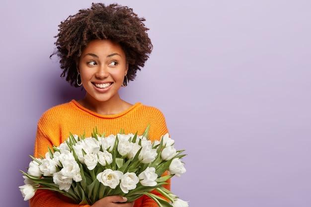 Studio shot di felice donna afro con capelli croccanti, sorride felicemente, guarda da parte, vestito con un maglione arancione