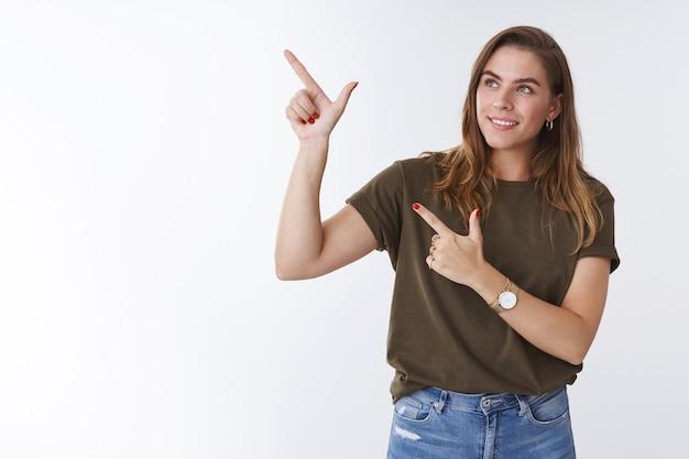 스튜디오 샷 행복한 카리스마 넘치는 매력적인 유럽 여성이 왼쪽 위 모서리를 옆으로 가리키는 검지 손가락으로 서비스 멋진 프로모션, 광고 제안 흰색 배경을 사용하여 즐겁게 웃고 있습니다.