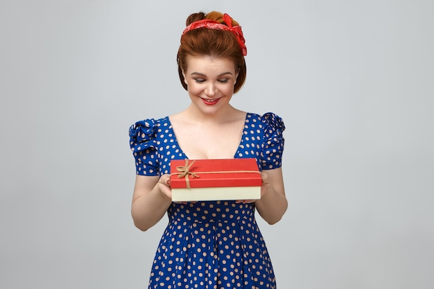 Studio shot of happy charming young caucasian female with retro hairstyle posing at blank wall, holding box, looking in anticipation, feeling impatient to open it. birthday and celebration concept