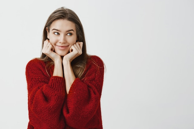 Studio shot of happy cute caucasian female coworker in stylish loose sweater, leaning on hands and looking aside with curious cheerful smile, being in good mood, waiting for her order in restaurant