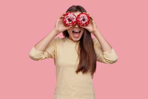 Studio shot di felice donna dai capelli scuri copre gli occhi con due ciambelle rosse, essendo in alto spirito, indossa abiti gialli