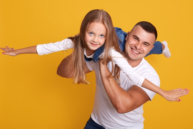 Studio shot of happy family father and daughter playing together, cute child wearing overalls pretending being plane with their hands