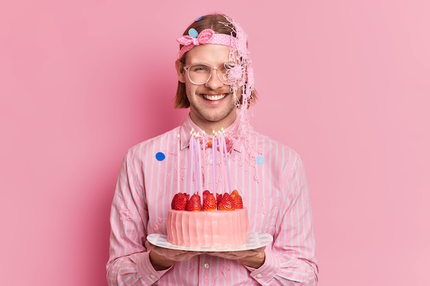 Studio shot of happy man celebrates birthday holds tasty strawberry cake meets guests dresed in festive clothes isolated over pink background