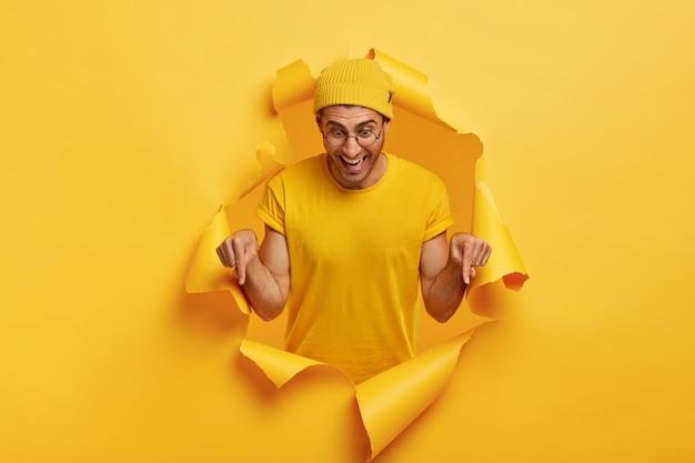 Studio shot di uomo felice con gioiosa espressione facciale, punta verso il basso sul pavimento, promuove qualcosa, mostra la direzione in basso