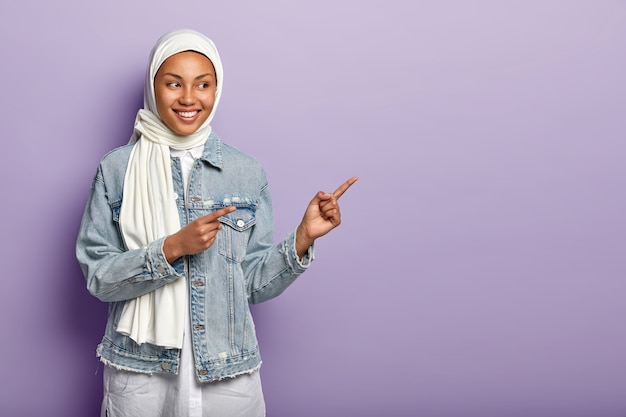 Studio shot of happy muslim woman points aside