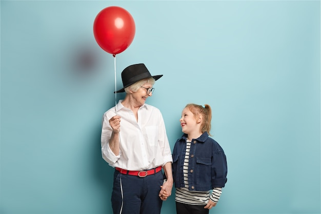 Studio shot of happy small child holds hand of grandmother with balloon, look at each other, spend free time