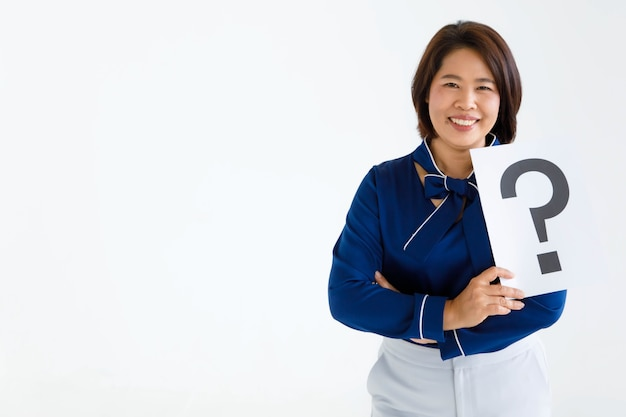 Studio shot of happy smiling female office staff in casual business wears stand crossed arms look at camera hold question mark paper cardboard sign in hands solving crisis problem on white background