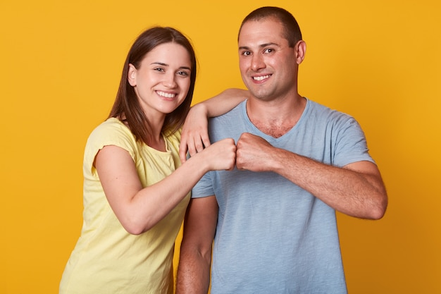 Studio shot of happy smiling young woman and man couple give fist bump looking at camera