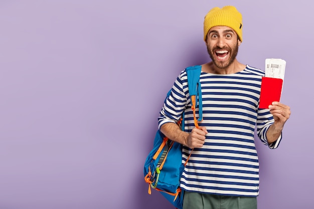 Studio shot of happy unshaven male backpacker holds passport with document, carries rucksack on shoulder, smiles gladfully, dressed in casual outfit, isolated over purple wall, ready for journey