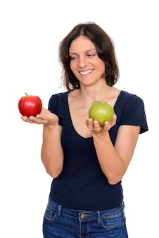 Studio shot of happy woman holding red and green apple isolated against white background